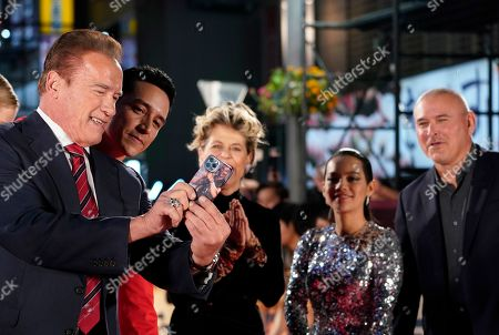 Arnold Schwarzenegger takes pictures with a smartphone next to US actor Gabriel Luna, US actress Linda Hamilton, Colombian actress Natalia Reyes and US film director Tim Miller during the Japanese premiere of 'Terminator: Dark Fate' in Tokyo, Japan, 06 November 2019. The movie will open in theaters across Japan on 08 November 2019.