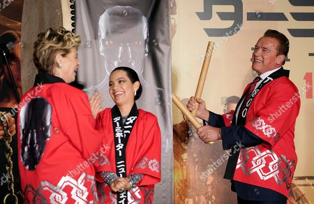 Stock Image of Arnold Schwarzenegger (R) hits a Japanese drum as US actress Linda Hamilton (L) and Colombian actress Natalia Reyes smile during the Japanese premiere of 'Terminator: Dark Fate' in Tokyo, Japan, 06 November 2019. The movie will open in theaters across Japan on 08 November 2019.