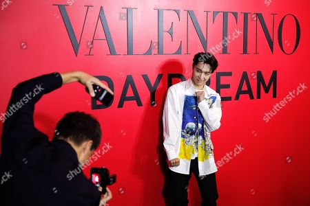 Stock Image of Chinese singer Zhang Yixing poses for a photographer during a cocktail party for the Valentino new flagship boutique store opening at Sanlitun Village shopping mall in Beijing