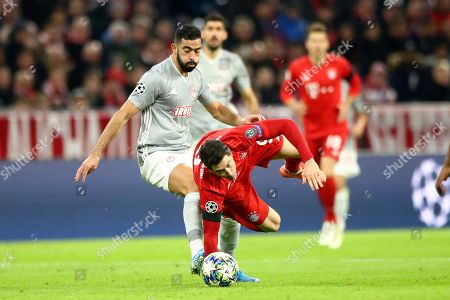 Olympiakos' Yassine Meriah, left, stops Bayern's Robert Lewandowski during the Champions League group B soccer match between Bayern Munich and Olympiakos in Munich, Germany