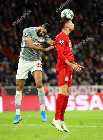 Olympiakos' Yassine Meriah, left, and Bayern's Leon Goretzka jump for the ball during the Champions League group B soccer match between Bayern Munich and Olympiakos in Munich, Germany