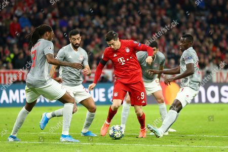 Olympiakos' Ruben Semedo, left, Yassine Meriah, second left, Andreas Bouchalakis, background, and Mady Camara try to stop Bayern's Robert Lewandowski during the Champions League group B soccer match between Bayern Munich and Olympiakos in Munich, Germany
