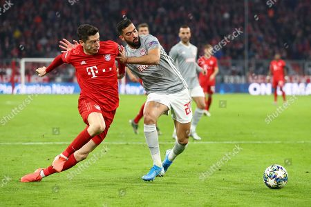 Bayern's Robert Lewandowski, left, and Olympiakos' Yassine Meriah fight for the ball during the Champions League group B soccer match between Bayern Munich and Olympiakos in Munich, Germany