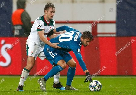 Lokomotiv's Brian Idowu, left, fights for the ball with Juventus' Rodrigo Bentancur during the Champions League Group D soccer match between Lokomotiv Moscow and Juventus at the Lokomotiv Stadium in Moscow, Russia