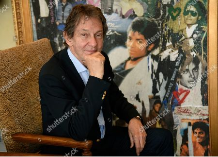 """Entertainment and corporate lawyer John Branca, the co-executor of Michael Jackson's estate, poses in his office next to an artwork presented to him from Sony Music commemorating the sale of 100 million copies of Michael Jackson's album """"Thriller,"""", at the law firm of Ziffren Brittenham LLP in Los Angeles"""