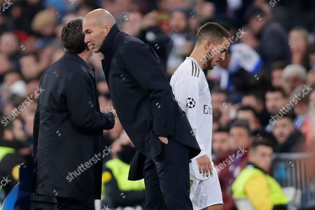 Real Madrid's Eden Hazard, right, walks past Real Madrid's head coach Zinedine Zidane after being substituted during a Champions League group A soccer match between Real Madrid and Galatasaray at the Santiago Bernabeu stadium in Madrid, Spain