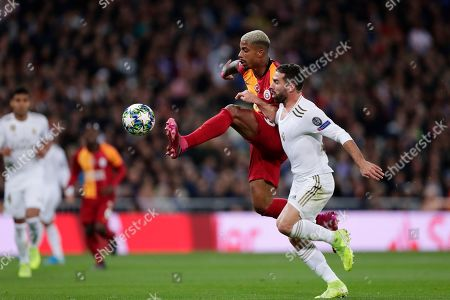 Galatasaray's Mario Lemina, centre and Real Madrid's Dani Carvajal challenge for the ball during a Champions League group A soccer match between Real Madrid and Galatasaray at the Santiago Bernabeu stadium in Madrid, Spain