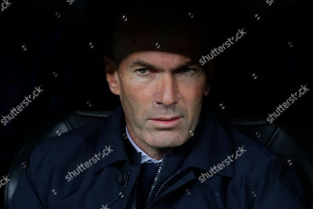 Real Madrid's head coach Zinedine Zidane takes his seat in the dugout prior to a Champions League group A soccer match between Real Madrid and Galatasaray at the Santiago Bernabeu stadium in Madrid, Spain