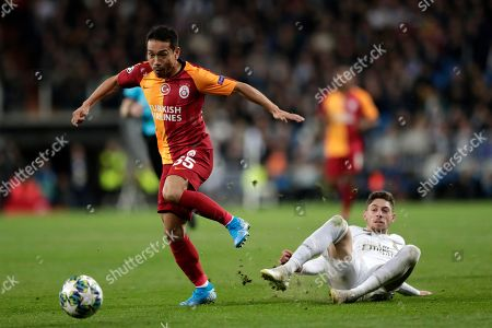 Real Madrid's Federico Valverde, right, tries to stop Galatasaray's Yuto Nagatomo during a Champions League group A soccer match between Real Madrid and Galatasaray at the Santiago Bernabeu stadium in Madrid