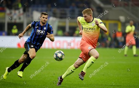 Manchester City's Kevin De Bruyne, right, challenges for the ball with Atalanta's Remo Freuler during the Champions League group C soccer match between Atalanta and Manchester City at the San Siro stadium in Milan, Italy