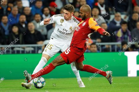 Stock Image of Galatasaray's Steven Nzonzi (R) in action against Real Madrid's Federico Valverde (L) during the UEFA Champions League group A soccer match between Real Madrid and Galatasaray Istanbul at the Santiago Bernabeu Stadium in Madrid, Spain, 06 November 2019.