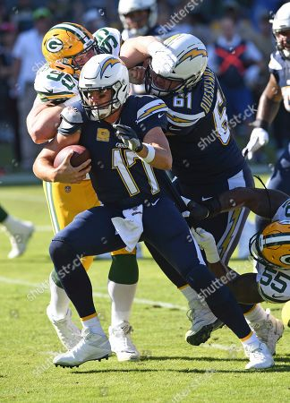 Los Angeles Chargers quarterback Philip Rivers (17) scrambles with the ball and tires to avoid being tackled during an NFL football game against the Green Bay Packers, in Carson, Calif. The Chargers defeated the Packers 26-11