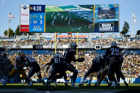 Los Angeles Chargers quarterback Philip Rivers, center, gets set to hand off the ball during the second half of an NFL football game against the Green Bay Packers, in Carson, Calif