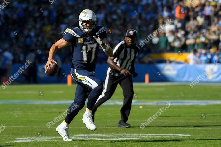 Los Angeles Chargers quarterback Philip Rivers runs with the ball during the first half of an NFL football game against the Green Bay Packers, in Carson, Calif