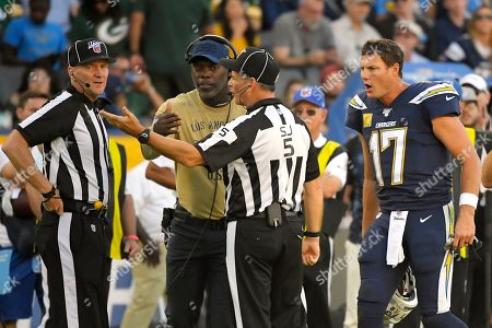 Los Angeles Chargers head coach Anthony Lynn, second from left, and quarterback Philip Rivers, right, talk over a play with officials during the second half of an NFL football game against the Green Bay Packers, in Carson, Calif
