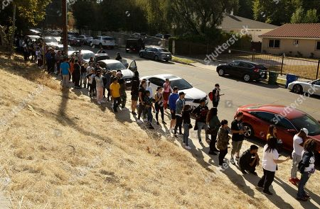 People line up around the block of singer Chris Brown's home in the Tarzana area of Los Angeles . Brown says he's having a high-end yard sale at his Los Angeles home, and a crowd has been gathering for hours. The singer posted a flyer on his Instagram and Twitter accounts that included his home address in the Tarzana neighborhood and says the event will start at 10 a.m Wednesday and go until 7 p.m
