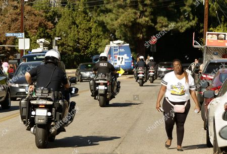 Los Angeles Police Motorcycle officers keep local transit moving past the block of singer Chris Brown's home in the Tarzana area of Los Angeles . Brown says he's having a high-end yard sale at his Los Angeles home, and a crowd has been gathering for hours. The singer posted a flyer on his Instagram and Twitter accounts that included his home address in the Tarzana neighborhood and says the event will start at 10 a.m Wednesday and go until 7 p.m