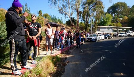People line up around the rear city block of singer Chris Brown's home in the Tarzana area of Los Angeles . Brown says he's having a high-end yard sale at his Los Angeles home, and a crowd has been gathering for hours. The singer posted a flyer on his Instagram and Twitter accounts that included his home address in the Tarzana neighborhood and says the event will start at 10 a.m Wednesday and go until 7 p.m