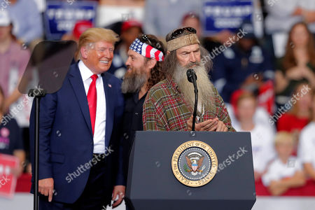 President Donald laughs with Willie Robertson, of the reality TV series Duck Dynasty, and Phil Roberston, the family patriarch, right, at a campaign rally in Monroe, La