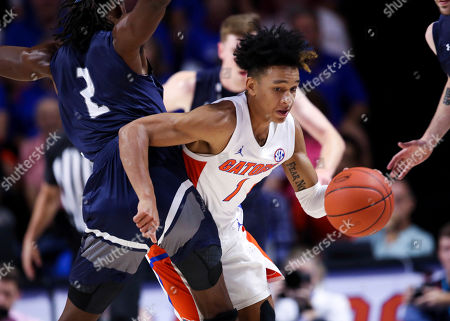 Stock Picture of Tre Mann, Wajid Aminu. Florida guard Tre Mann (1) dribbles around North Florida forward Wajid Aminu (2) during the second half of an NCAA college basketball game, in Gainesville, Fla