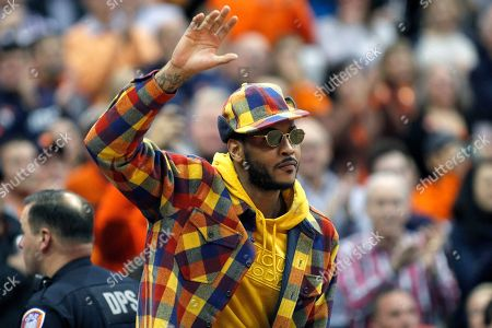 Former Syracuse basketball great Carmelo Anthony waves to the crowd during the first half of an NCAA college basketball game against Virginia in Syracuse, N.Y