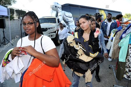 Bejaney McDonald, Mehrzad Mozhdekanloo. Bejaney McDonald, left, and Mehrzad Mozhdekanloo, both from Los Angeles, stand in line to purchase items at Chris Brown's yard sale at Brown's home in the Tarzana neighborhood of the San Fernando Valley, in Los Angeles