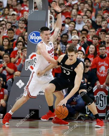Cincinnati's Chris Vogt, right, posts up against Ohio State's Kyle Young during the second half of an NCAA college basketball game, in Columbus, Ohio. Ohio State beat Cincinnati 64-56
