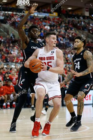 Ohio State's Kyle Young, center, looks for an open pass as Cincinnati's Tre Scott, left, and Jarron Cumberland defend during the second half of an NCAA college basketball game, in Columbus, Ohio. Ohio State beat Cincinnati 64-56