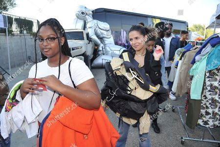 Bejaney McDonald, Mehrzad Mozhdekanloo. Bejaney McDonald, left, and Mehrzad Mozhdekanloo both from Los Angeles stand in line to purchase items at Chris Brown's yard sale at Brown's home in the Tarzana neighborhood of the San Fernando Valley, in Los Angeles