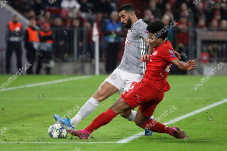 Stock Photo of Bayern's Serge Gnabry, foreground, and Olympiakos' Yassine Meriah challenge for the ball during the Champions League group B soccer match between Bayern Munich and Olympiakos in Munich, Germany
