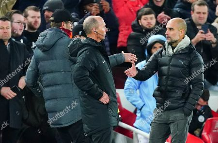 Liverpool manager Jurgen Klopp and Manchester City Manager Pep Guardiola shake hands behind fourth official Mike Dean