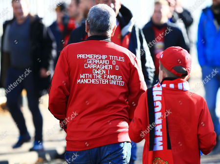 Stock Photo of A Manchester United fan arrives wearing a jacket aimed at Steven Gerrard and Jamie Carragher