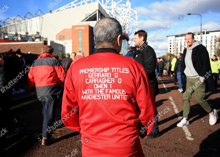 A Manchester United fan arrives wearing a jacket aimed at Steven Gerrard and Jamie Carragher
