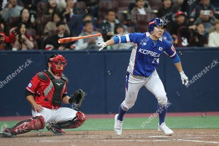 South Korea's Park Min-woo hurls his bat after hitting an RBI single off Canada's pitcher Dustin Molleken during the 9th inning of the group C of the WBSC Premier12 2019 world baseball tournament at Gocheok Sky Dome in Seoul, South Korea