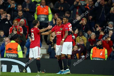 Manchester United's Anthony Martial, center, celebrates with Juan Mata and Marcus Rashford, right, after scoring his side's second goal during the Europa League group L soccer match between Manchester United and FK Partizan at Old Trafford Stadium in Manchester, England