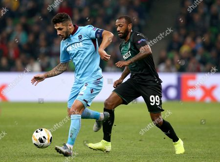 Trabzonspor's Kamil Corekci, left, and Krasnodar's Manuel Fernandes challenge for the ball during the Europa League Group C soccer match between Trabzonspor and F? Krasnodar in Krasnodar, Russia