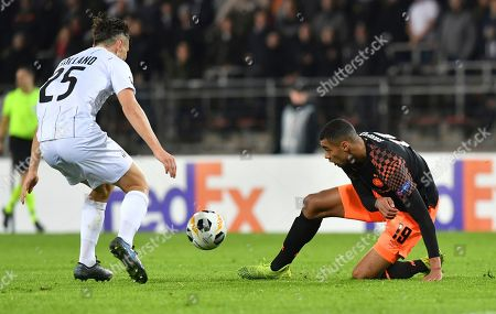 LASK's James Holland, left, and PSV's Cody Gakpo vie for the ball during the Europa League Group D soccer match between LASK Linz and PSV Eindhoven at the Linz Stadium in Linz, Austria