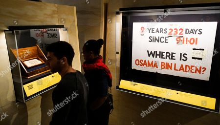 Stock Picture of People look at a brick from Osama Bin Laden?s compound in Pakistan (L) and a homemade sign that hung at a house in Brooklyn, New York (R) at the 9/11 Memorial Museum in New York, New York, USA, 07 November 2019. The exhibit, which opens on 15 November 2019, looks at the United States? decades-long search for Bin Laden which culminated with the Seal Team Six raid on his hideout in Pakistan in 2011.