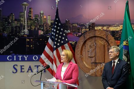 Stock Photo of Seattle Mayor Jenny Durkan, left, talks to reporters as city attorney Pete Holmes, right, looks on during a news conference, in Seattle. Durkan said Thursday that the city will file a lawsuit to block the $30 car tab initiative sponsored by anti-tax activist Tim Eyman that was passed by Washington voters in Tuesday's general election. Durkan said that if fully implemented, Initiative 976 would force the city to cut more than 100,000 bus hours and would hamper free bus access for students and low-income residents