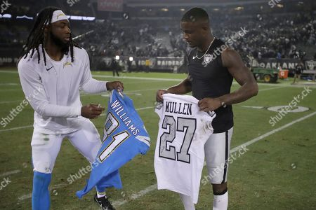 Stock Image of Los Angeles Chargers wide receiver Mike Williams, left, exchanges jerseys with Oakland Raiders cornerback Trayvon Mullen after an NFL football game in Oakland, Calif