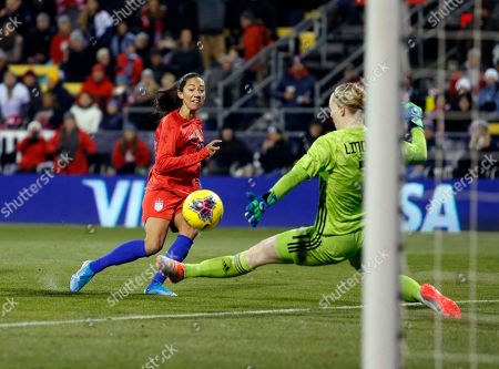 United States forward Christen Press, left, scores past Sweden goalkeeper Hedvig Lindahl during the first half of a women's international friendly soccer match in Columbus, Ohio
