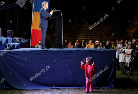 In this, a child gestures next to the stage where former prime minister and Plus leader, Dacian Ciolos addresses supporters of Dan Barna, the presidential candidate of the USR-Plus Alliance at a rally in Bucharest, Romania. Romania will hold presidential elections on Nov. 10, 2019