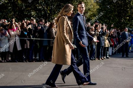 Lara Trump, the wife of Eric Trump, left, and President Donald Trump's White House senior adviser Jared Kushner, right, walk to across the South Lawn to join President Donald Trump on Marine One outside the White House in Washington, for a short trip to Andrews Air Force Base, Md. and then on to Georgia to meet with supporters