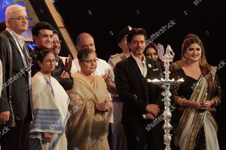 Stock Photo of President of Board of Control for Cricket in India (BCCI) Sourav Ganguly, left back, Chief Minister of West Bengal state Mamata Banerjee, second left, Bollywood actor Rakhee Gulzar, center, and Shah Rukh Khan, second right, attend the lamp lighting ceremony during the inauguration of the 25th Kolkata International Film Festival in Kolkata, India, . The festival will continue till Nov. 15