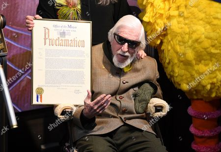 Puppeteer Caroll Spinney receives a proclamation from the New York City Mayor's office during the ceremonial lighting of the Empire State Building in honor of Sesame Street's 50th anniversary, in New York