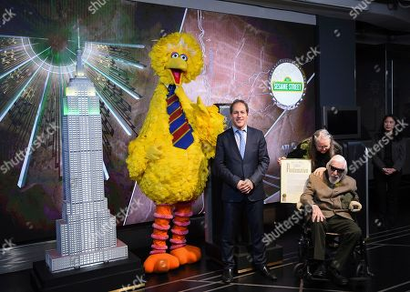 Stock Image of Steve Youngwood, Debra Spinney, Caroll Spiney. Sesame Street's Big Bird, Sesame Workshop president of media & education and CEO Steve Youngwood with Debra Spinney and puppeteer Caroll Spinney, seated right, participate in the ceremonial lighting of the Empire State Building in honor of Sesame Street's 50th anniversary, in New York