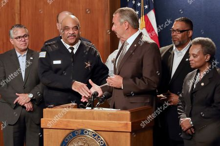 Former Los Angeles police Chief Charlie Beck, center, shakes hands with outgoing Superintendent Eddie Johnson, second from left, after he was named Chicago's interim police superintendent, in Chicago. Chicago Mayor Lori Lightfoot, right, made the announcement a day after Johnson said he would retire after more than three years as the city's police chief and more than 30 years with the department