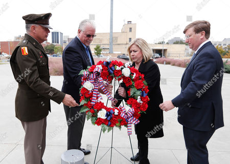 Stock Image of Janson D. Boyles, Tate Reeves, Eddie Smith, Jenny Smith. Major Gen. Janson D. Boyles, adjutant general of Mississippi, left, and Gov.-elect Tate Reeves, right, assist Gold Star family members Eddie Smith, second from left, and wife, Jenny Smith, in the laying of a memorial wreath in Entergy Plaza, in Jackson, Miss., during an early Veterans Day ceremony. The Smith's lost their son, Marine Staff Sgt. Jason A. Rogers, in an explosion two days before what would have been his 29th birthday, in April 7, 2011