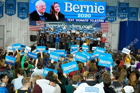 Supporters hold up Bernie Sanders signs for a photographer on stage prior to an election rally with Democratic presidential candidate Sen. Bernie Sanders, I-Vt., and Rep. Alexandria Ocasio-Cortez, D-N.Y., on the campus of Iowa Western Community College in Council Bluffs, Iowa