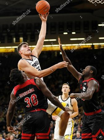 Luka Garza, Anselm Uzuegbunem, Brandon Jackson. Iowa center Luka Garza shoots over SIU-Edwardsville's Anselm Uzuegbunem (30) and Brandon Jackson, right, during the first half of an NCAA college basketball game, in Iowa City, Iowa